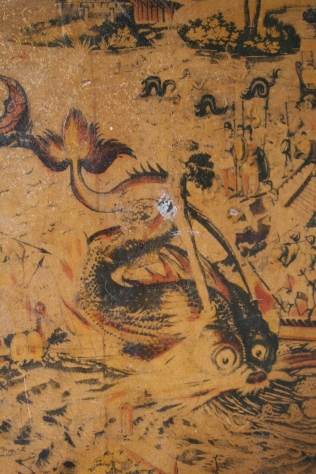 The serpent is being attacked by the warriors in the boat on the right.  Mermaids in the background, other soldiers standing at the ready.